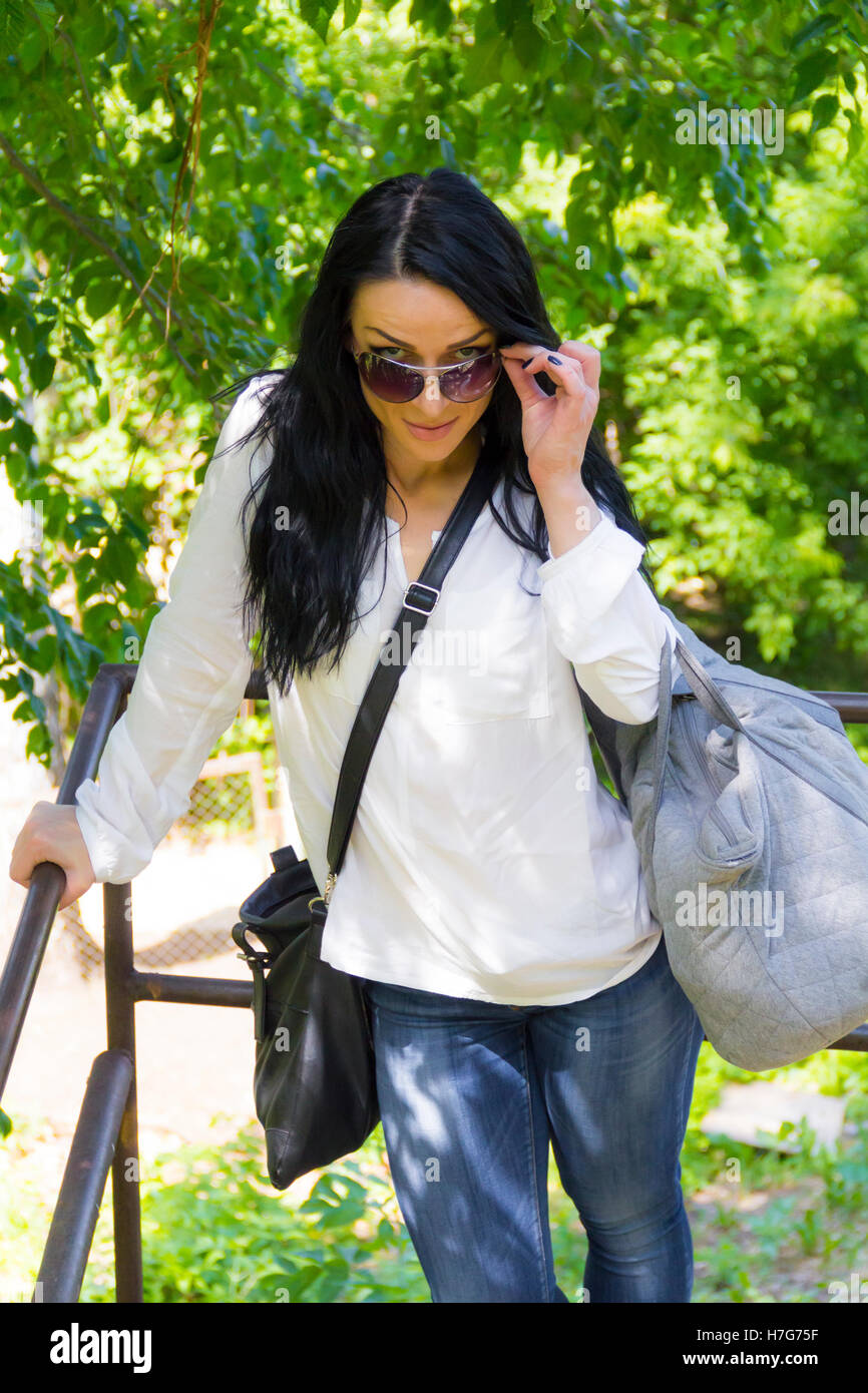 Tired European woman with bags in sunglass - Stock Image