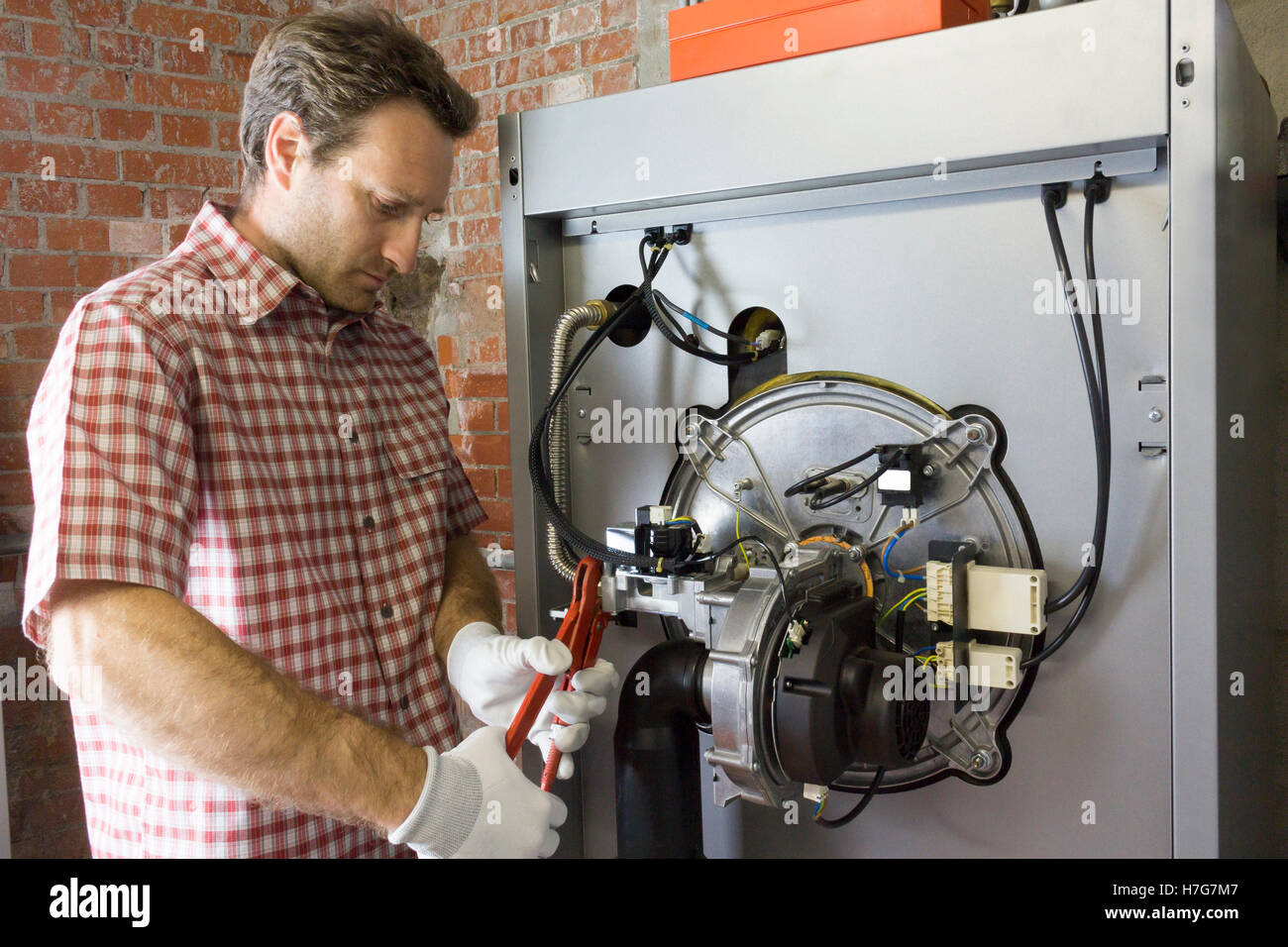 plumber who carries out the maintenance of a condensing boiler - Stock Image