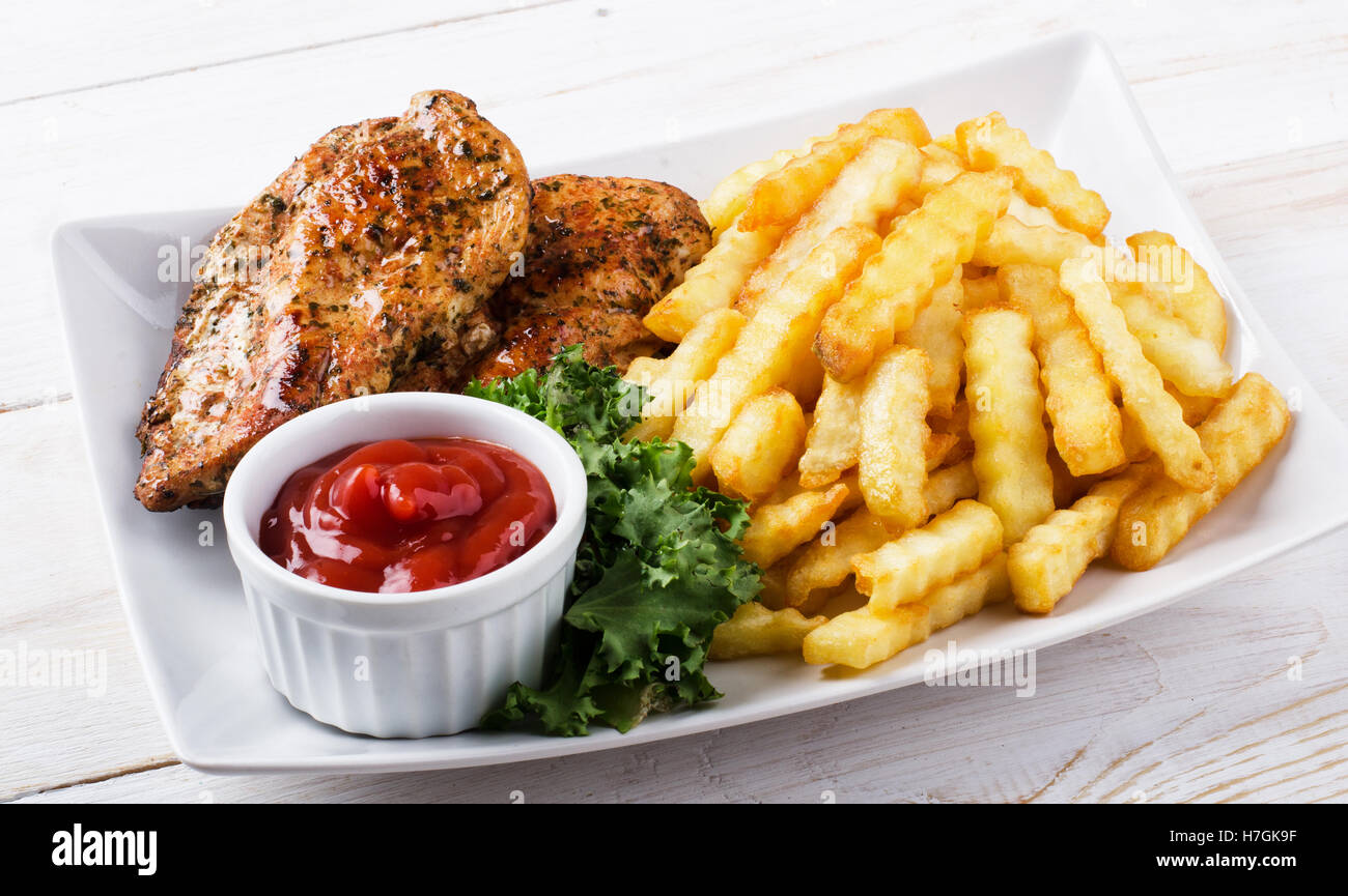 Grilled chicken steak, french fries and salad - Stock Image