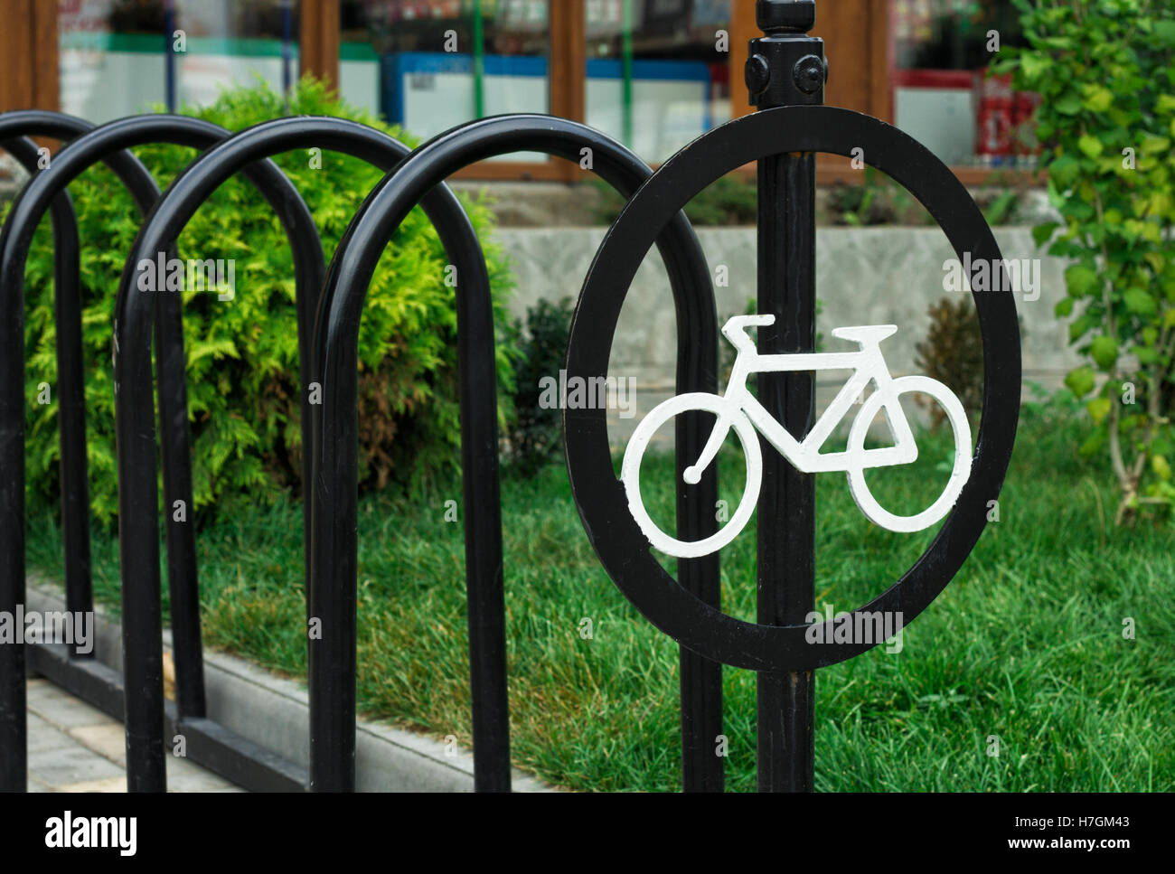 A round sign with a white Bicycle. Parking lot is empty - Stock Image