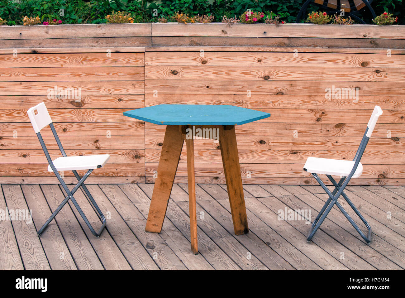 Two empty white modern chairs with blue table on the wooden floor of the theatre. Nobody is sitting. - Stock Image
