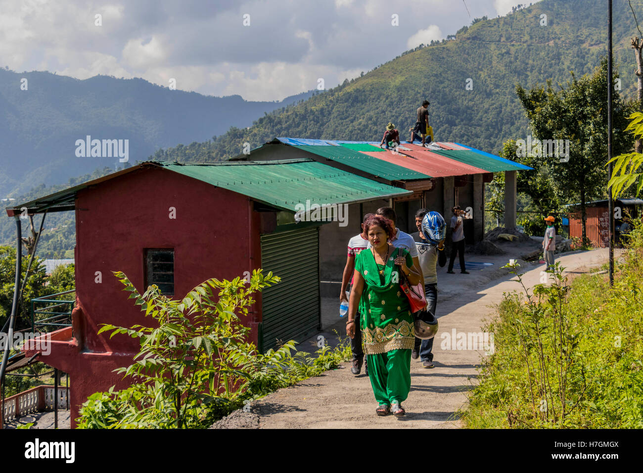 People walking and workers repairing roofs on the hillside overlooking the city of Pokhara Nepal - Stock Image