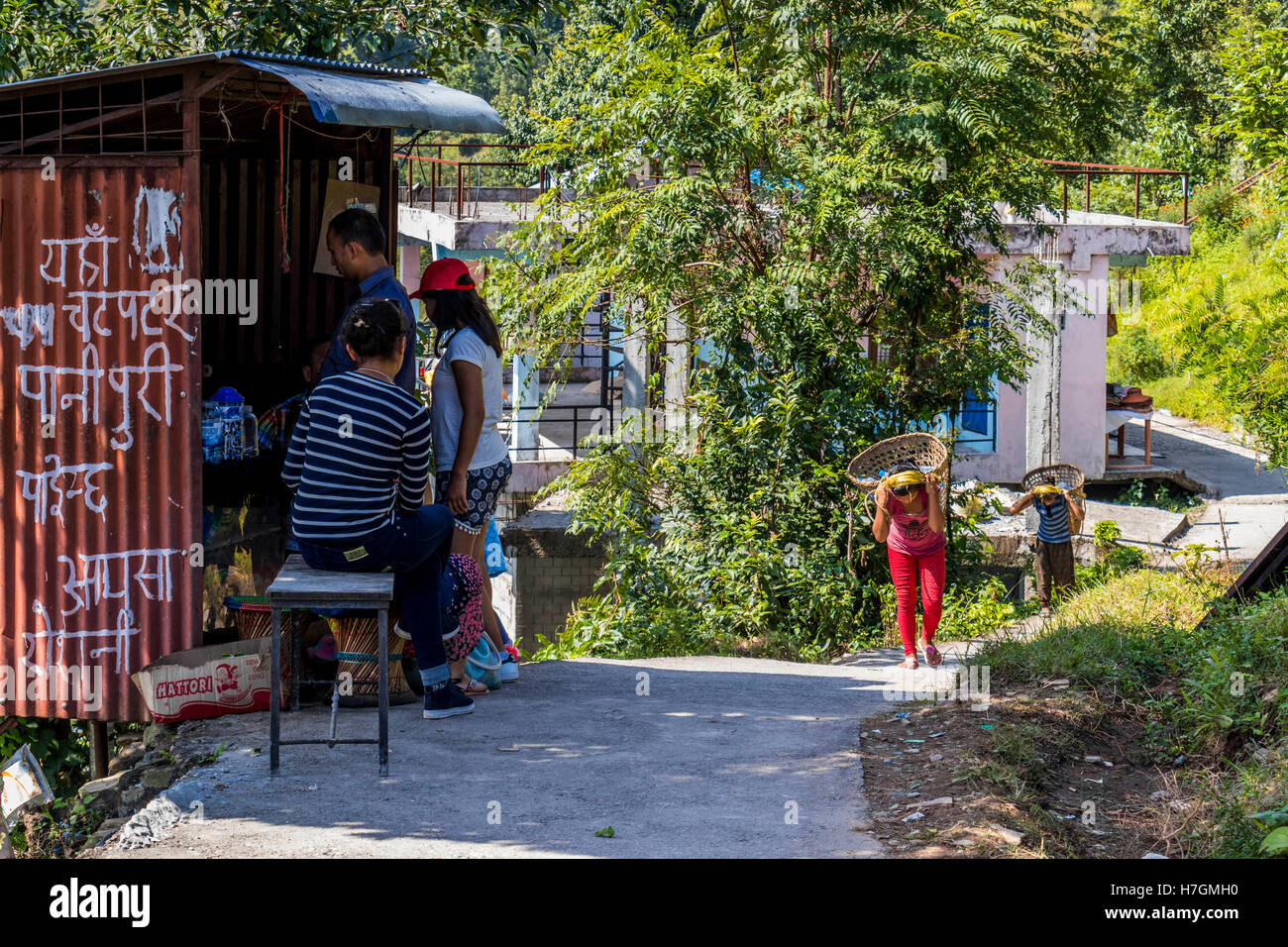 Workers carrying goods to the shops, while others sell goods from the small units in Pokhara Nepal - Stock Image