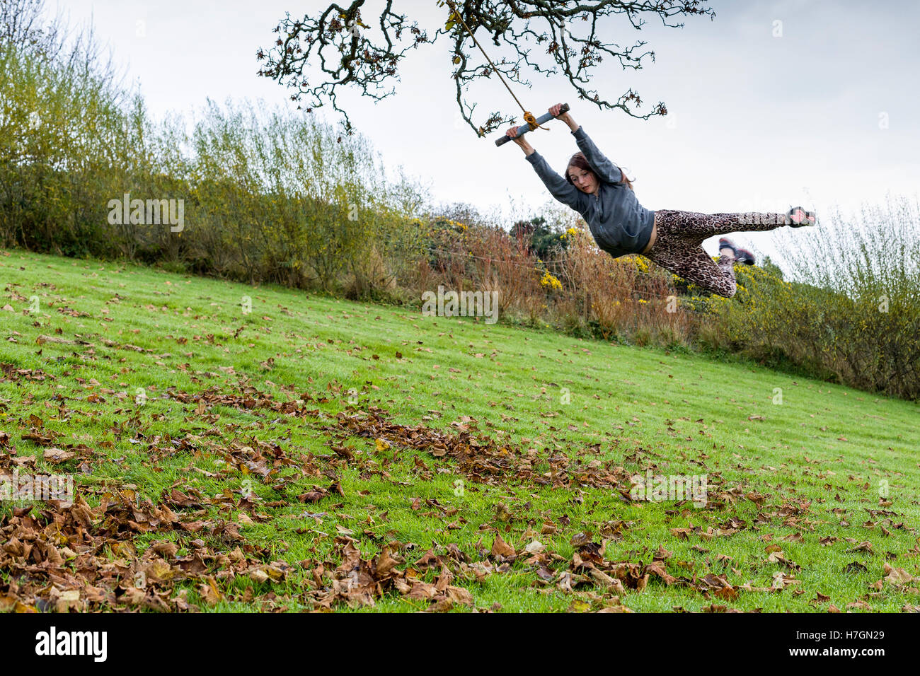 Teenage girl swinging on a rope swing outdoors  Model Release: Yes.  Property Release: Yes. - Stock Image