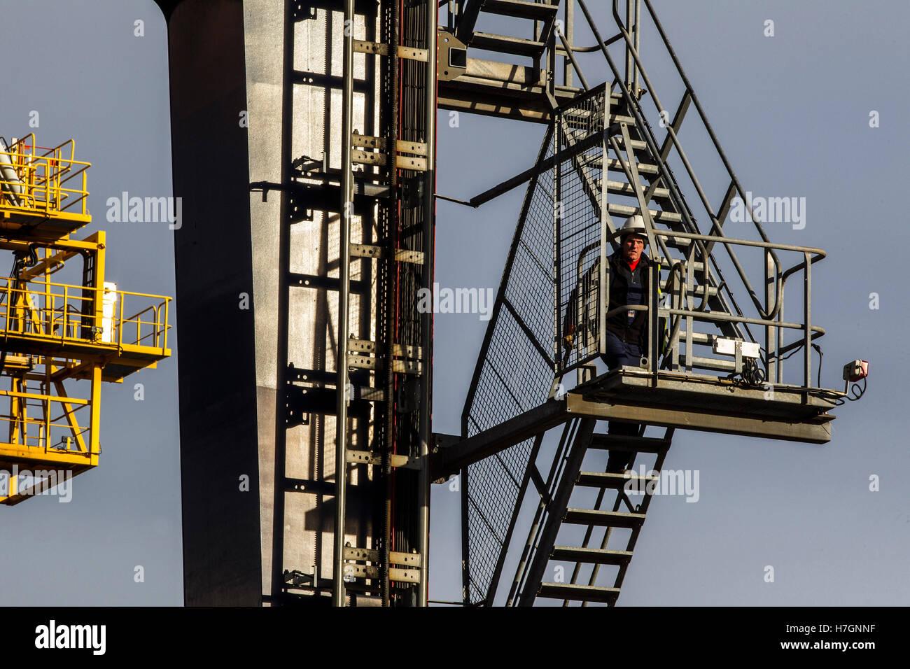 Man climbing ladder on large dock crane at Grangemouth - Stock Image