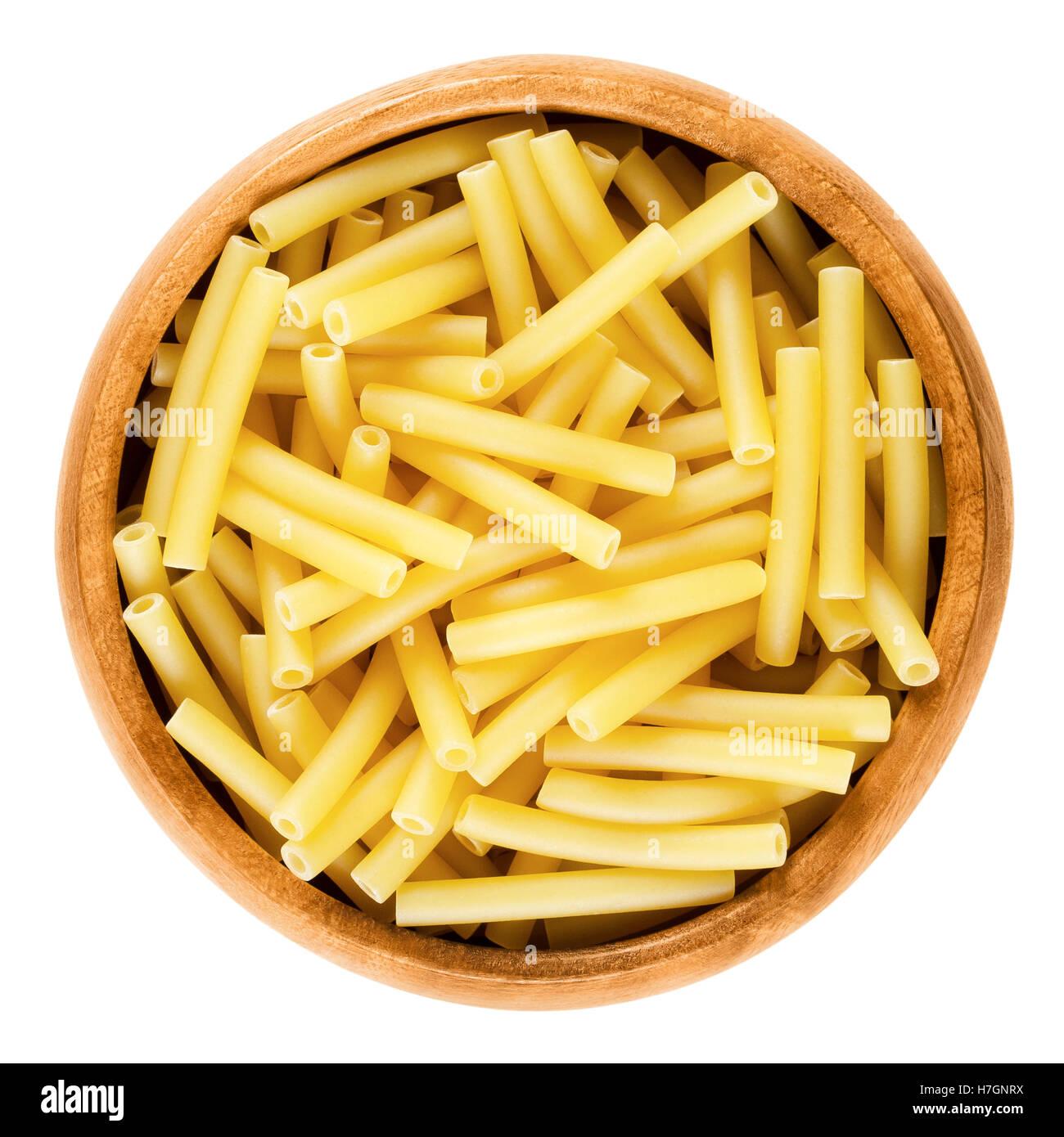 Macaroni pasta in wooden bowl, Italian maccheroni, short-cut noodles in the shape of narrow tubes. - Stock Image