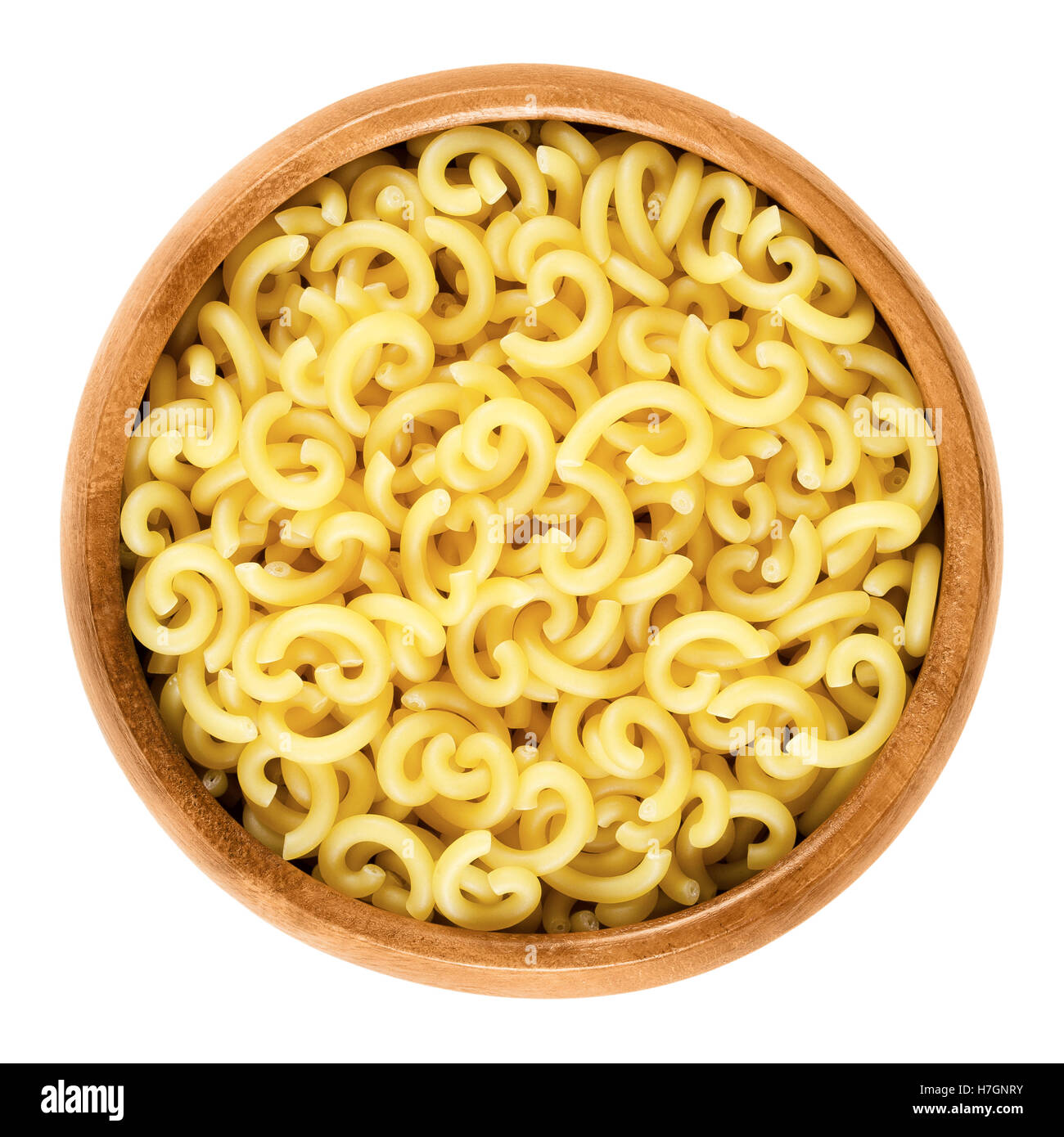 Gobbetti pasta in wooden bowl. Italian noddles, short-cut and G-shaped helical bent tubes. - Stock Image