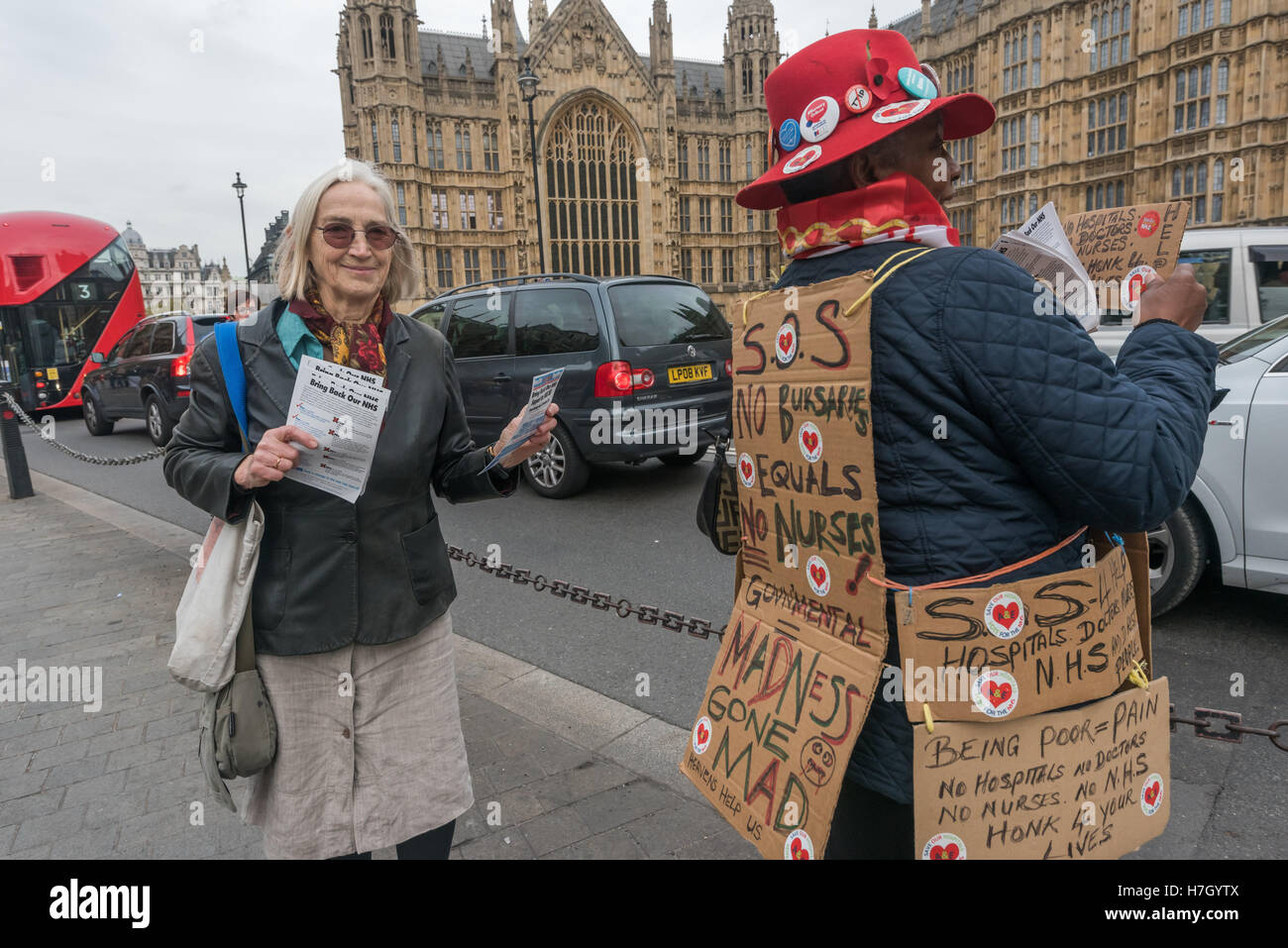 London, UK. 4 November 2016. A campaigner from Save Our Hospitals stands by the road with posters around her body - Stock Image