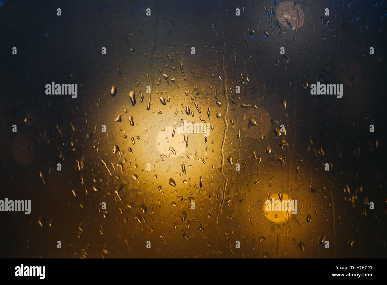 Blurred lights through steamy window with raindrops, dark background, selective focus - Stock Image