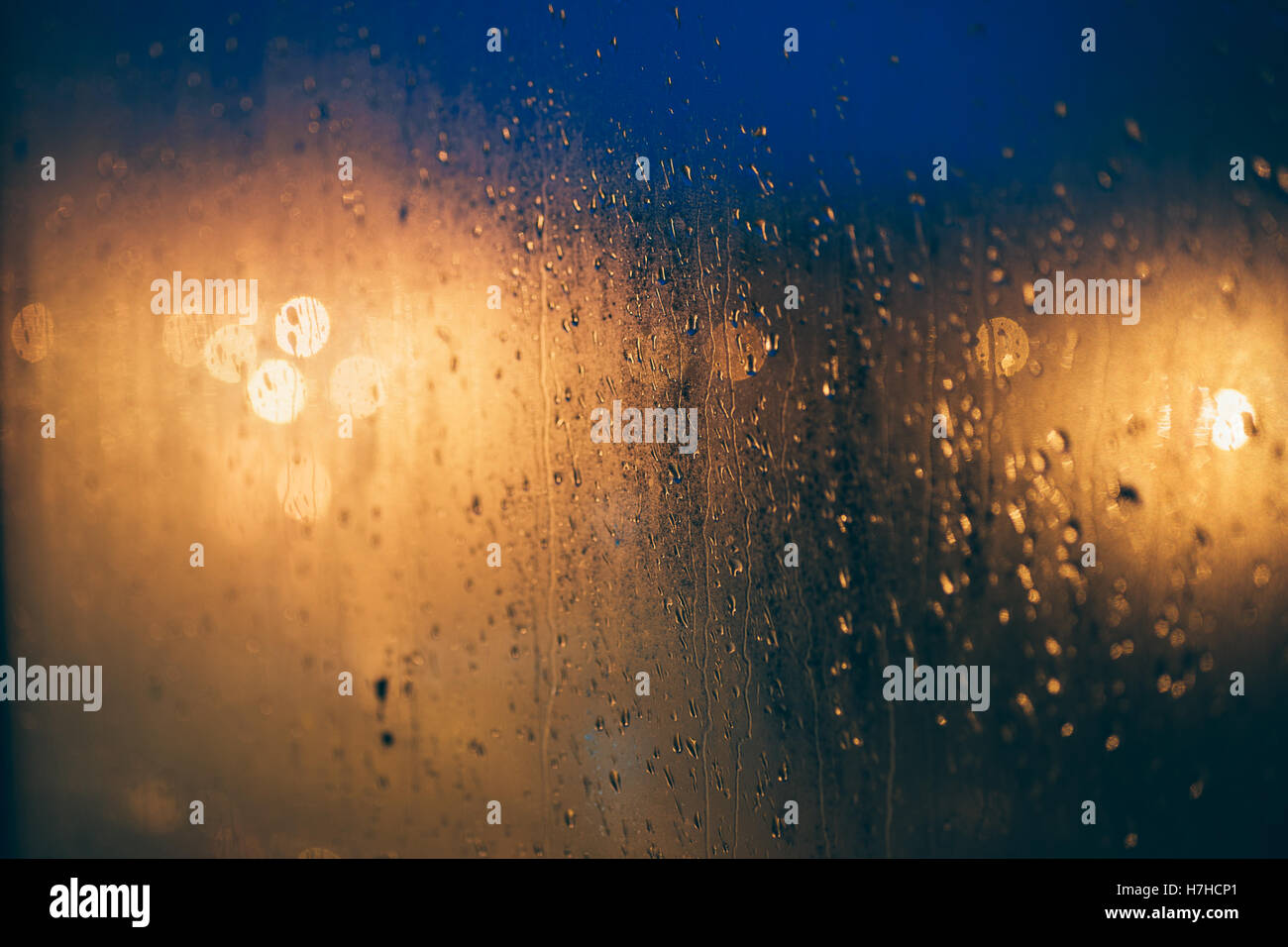 Abstract background of blurred lights through steamy window with waterdrops, selective focus - Stock Image