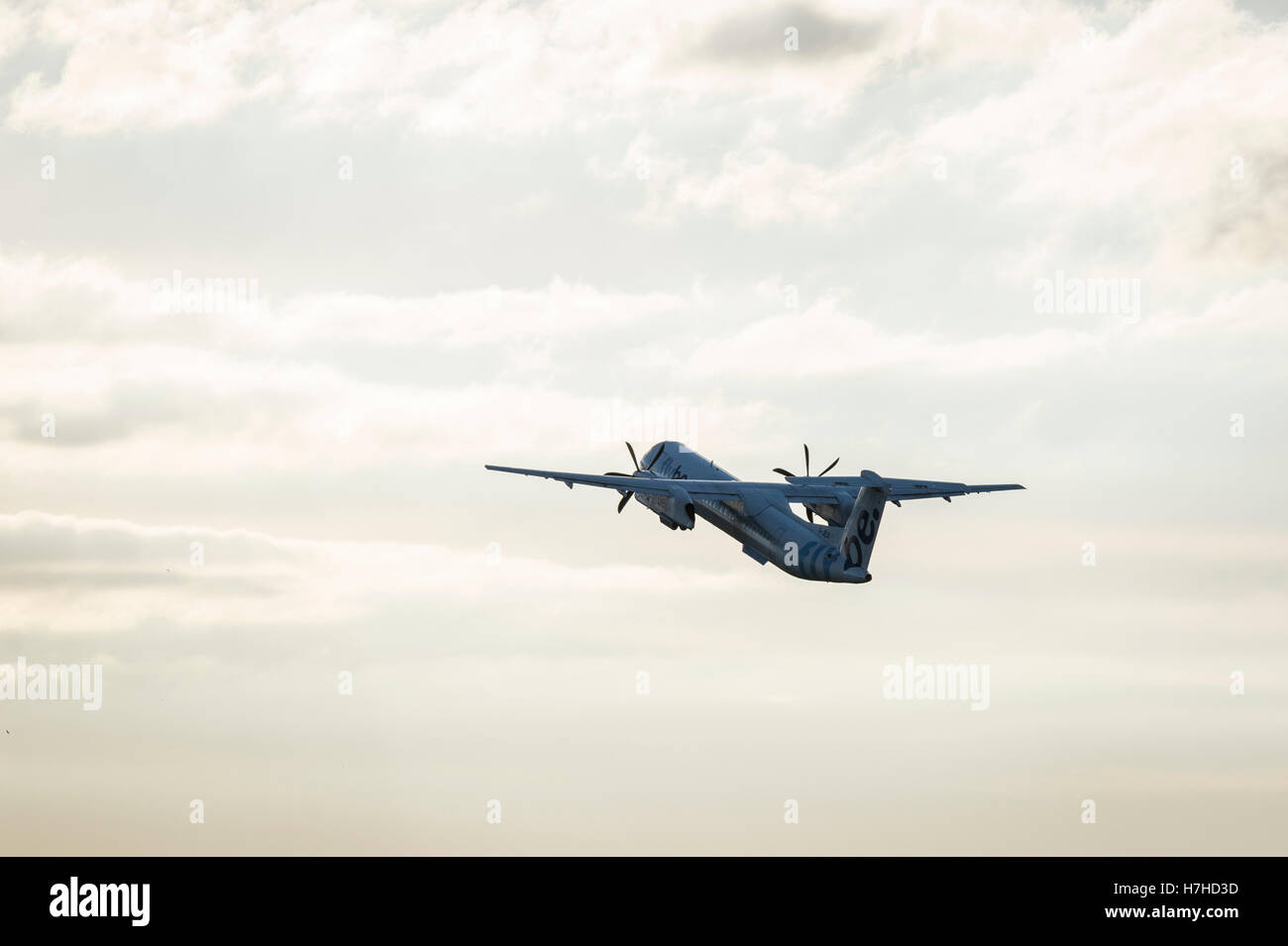 A Flybe Bombardier Q400 Dash-8 turboprop takes-off from Exeter Airport. - Stock Image