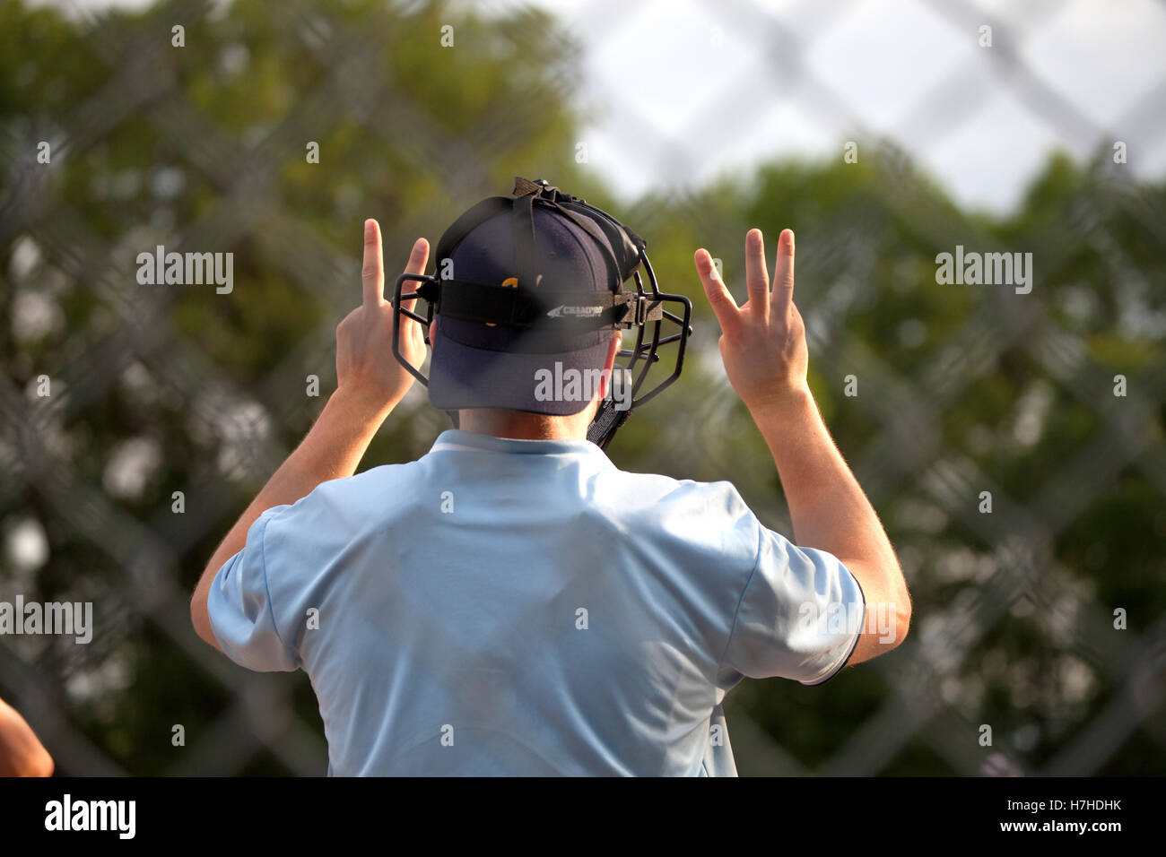 umpire in youth baseball game indicates full count with two fingers