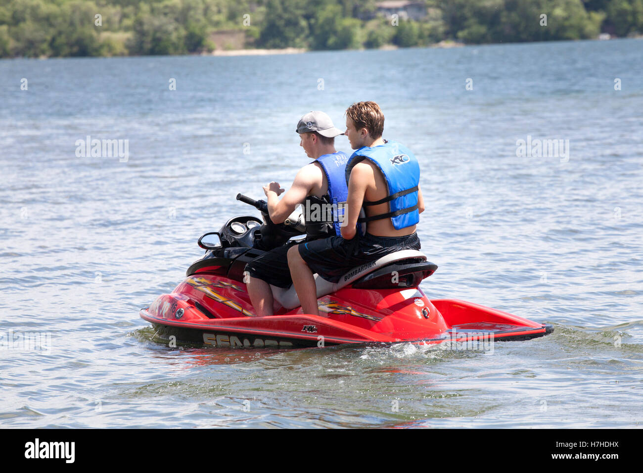 Two teenage boys wearing life vests driving Sea-Doo personal watercraft PWC on the lake. Clitherall Minnesota MN - Stock Image