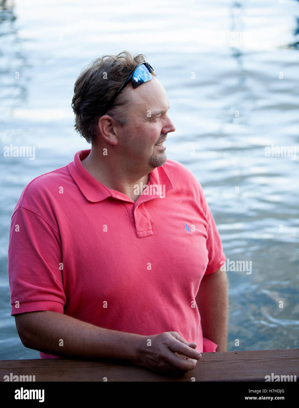 Handsome man standing in the water near the dock relaxing after doing waterfront chores. Clitherall Minnesota MN - Stock Image