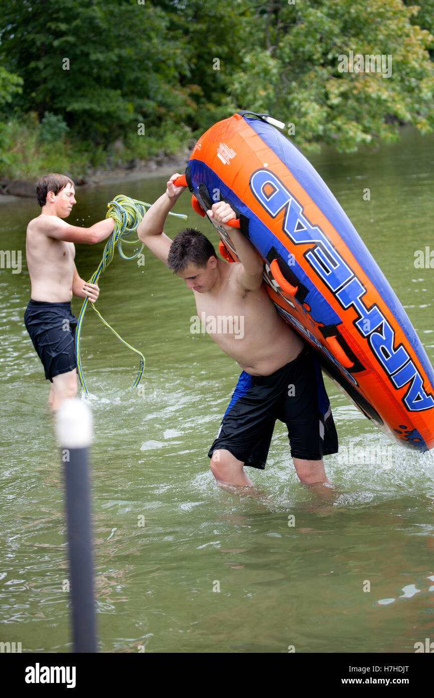 Teen boys bringing in Airhead Super Slice Water Sport Tube and winding tow rope after a great run. Clitherall Minnesota - Stock Image