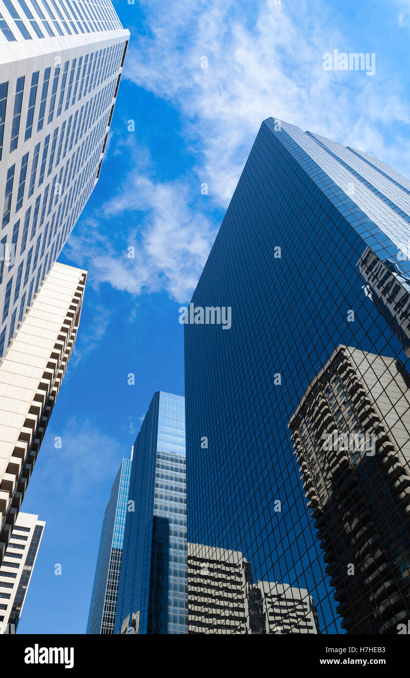 Tall corporate skyscrapers rise up to the skies in a city downtown. - Stock Image