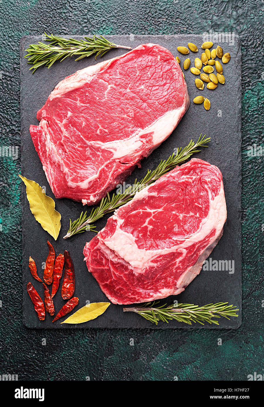 Two pieces of raw meat beef on a slate plate with rosemary - Stock Image