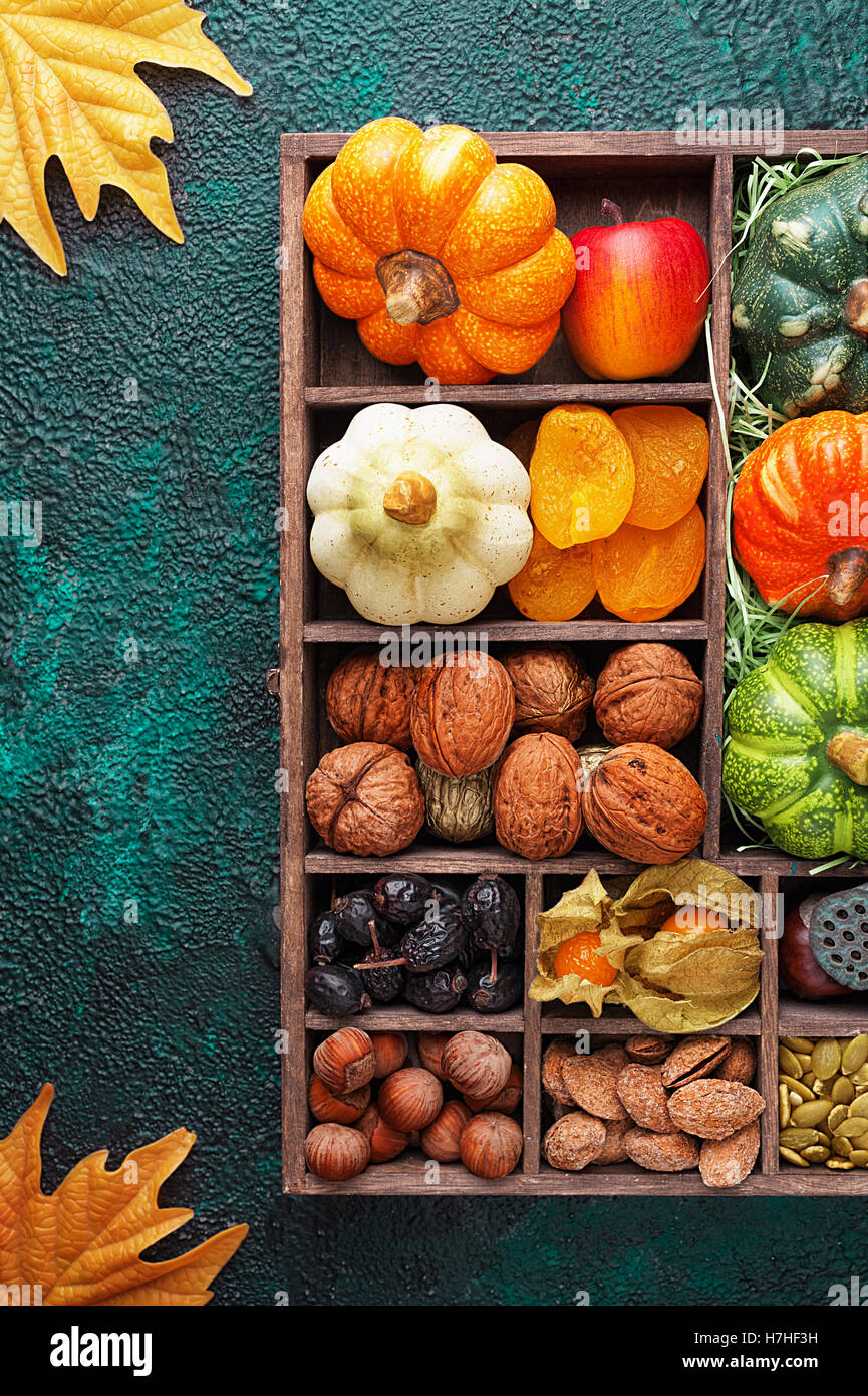 Set of autumn vegetables, fruits, nuts and seeds in a wooden box with cells top view with copy space - Stock Image