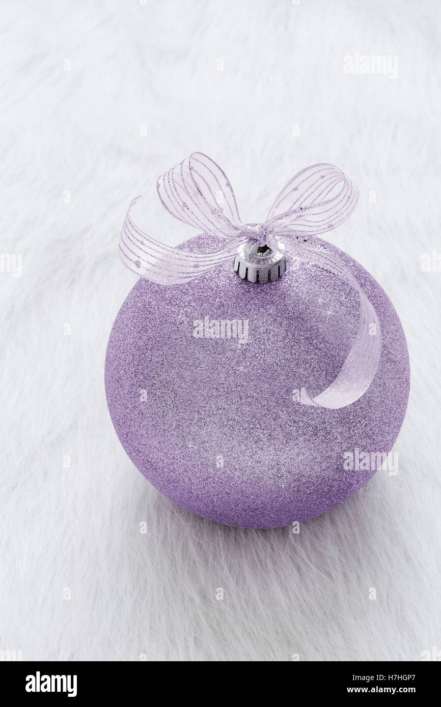 One beautiful, fancy,  perfect, sparkly, shiny, purple glitter Christmas ornament on vertical white background - Stock Image