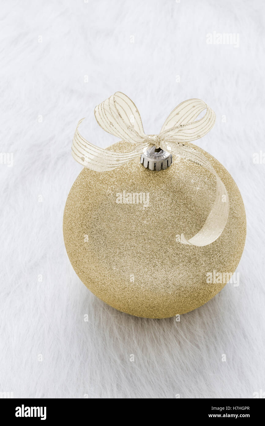 One beautiful, fancy,  perfect, sparkly, shiny, gold glitter Christmas ornament on vertical white background - Stock Image