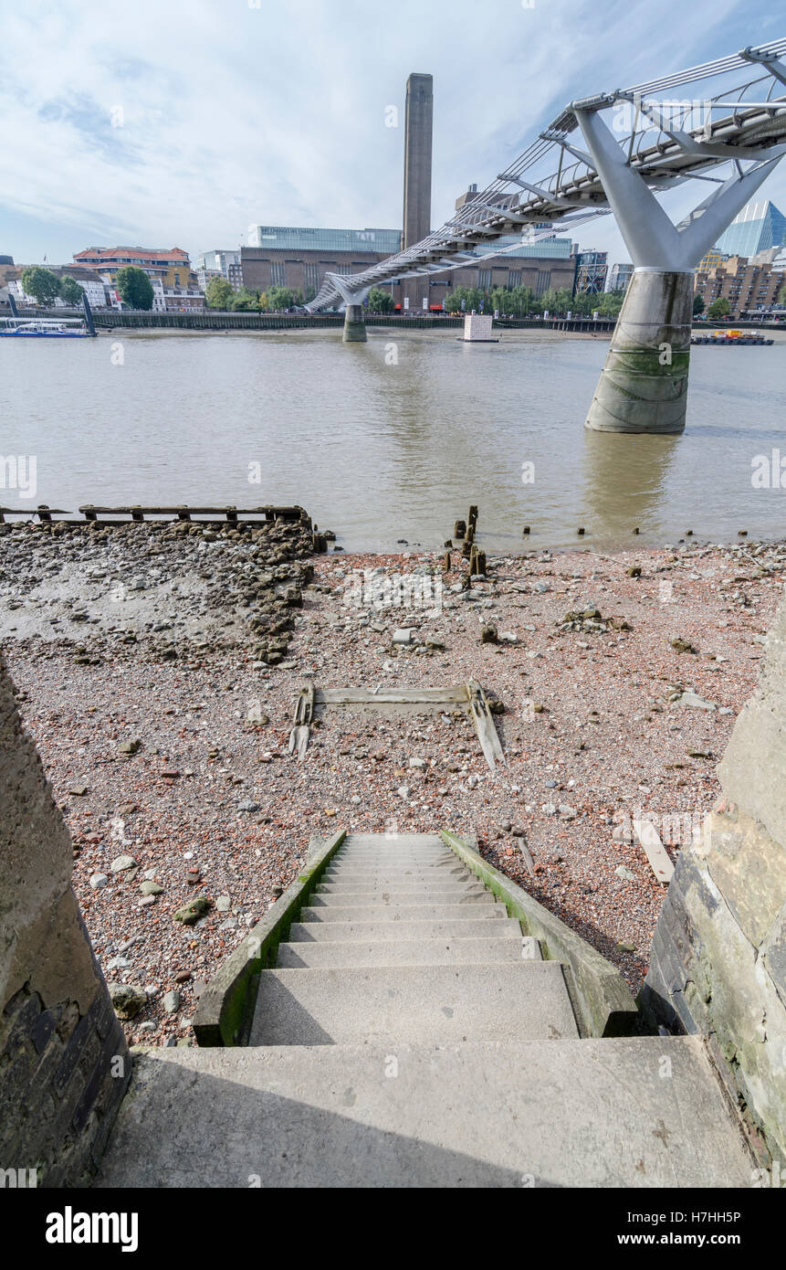 North bank of the River Thames at low tide under Millennium Bridge Stock Photo