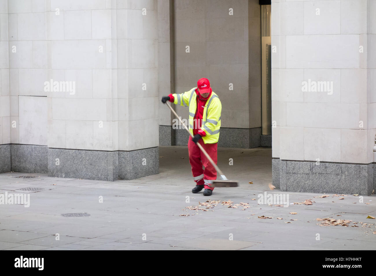 Workman sweeping leaves in St Paul's Churchyard, City of London, UK - Stock Image