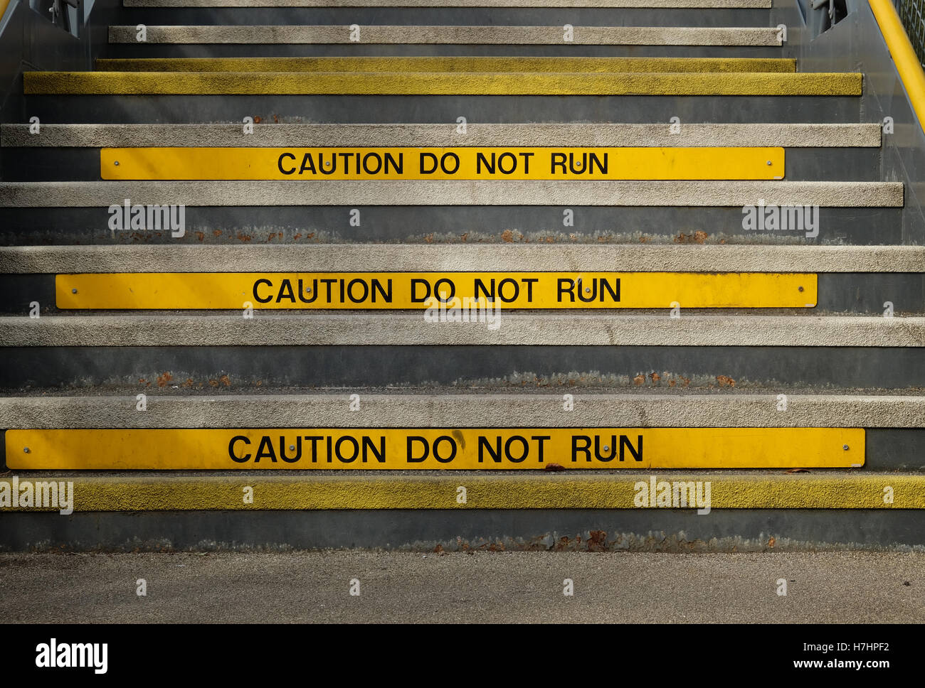 steps on a metal bridge with caution signs - Stock Image