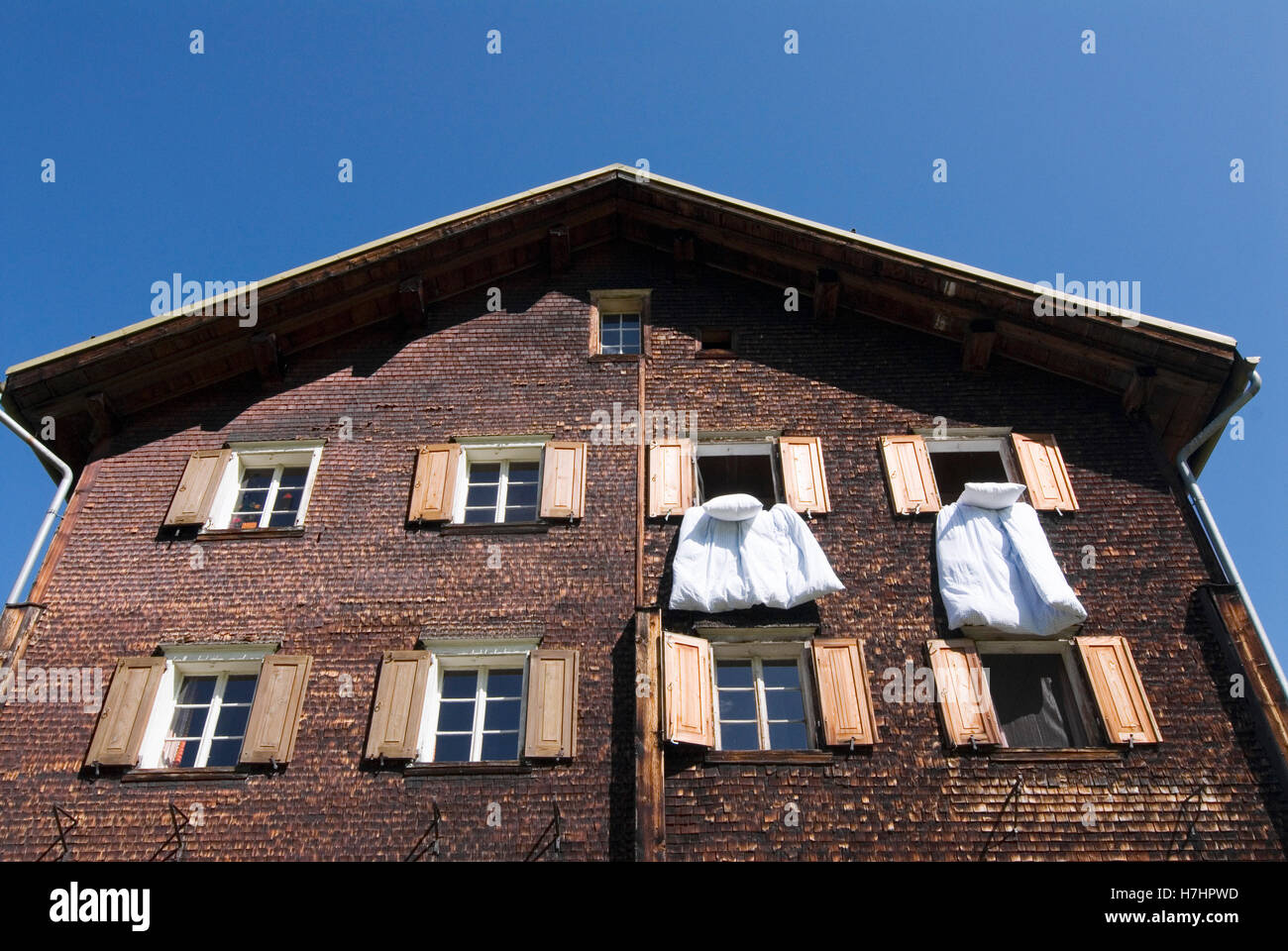 Bedlinen hanging out of the windows in a wooden house in Glas, canton of Grisons, Switzerland, Europe - Stock Image