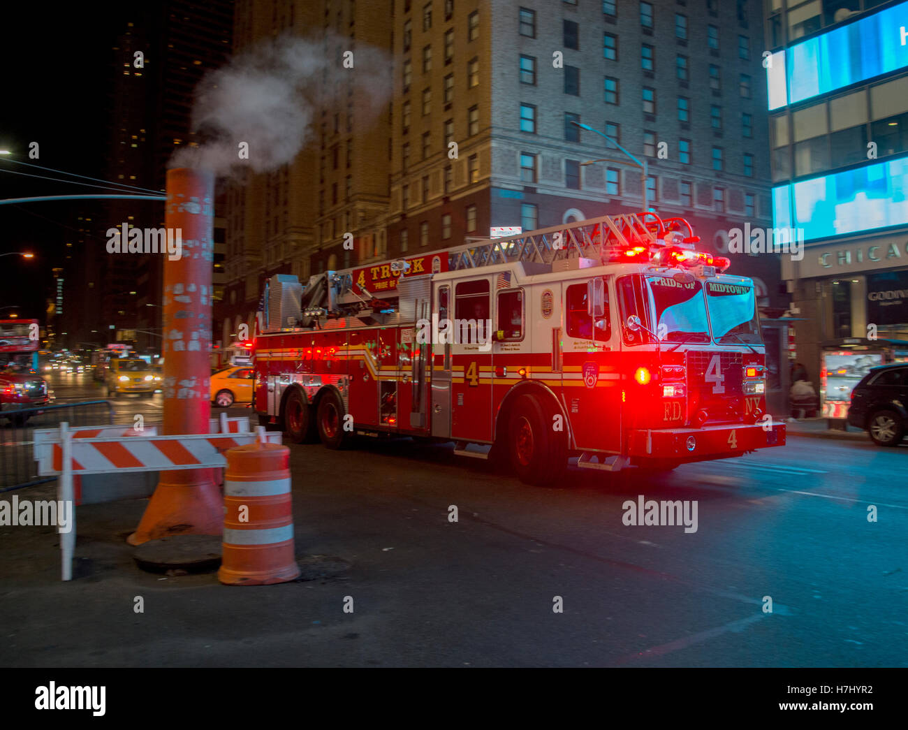 New York fire truck rushes past a steam vent on 7th Avenue - Stock Image