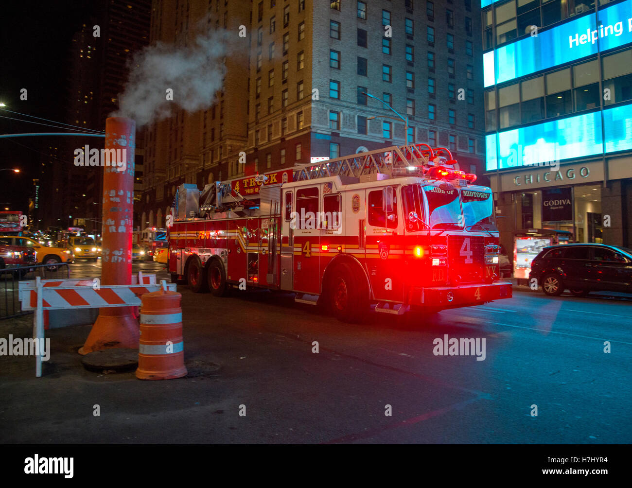 New York fire truck rushes past a steam vent on 7th Avenue Stock Photo
