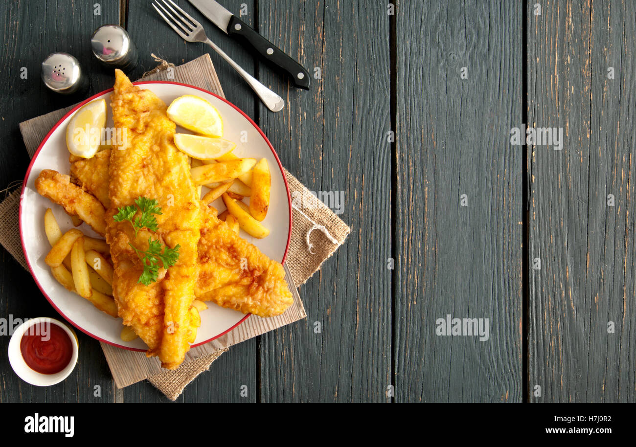 Two pieces of battered fish on a plate with chips on a wooden table with space - Stock Image