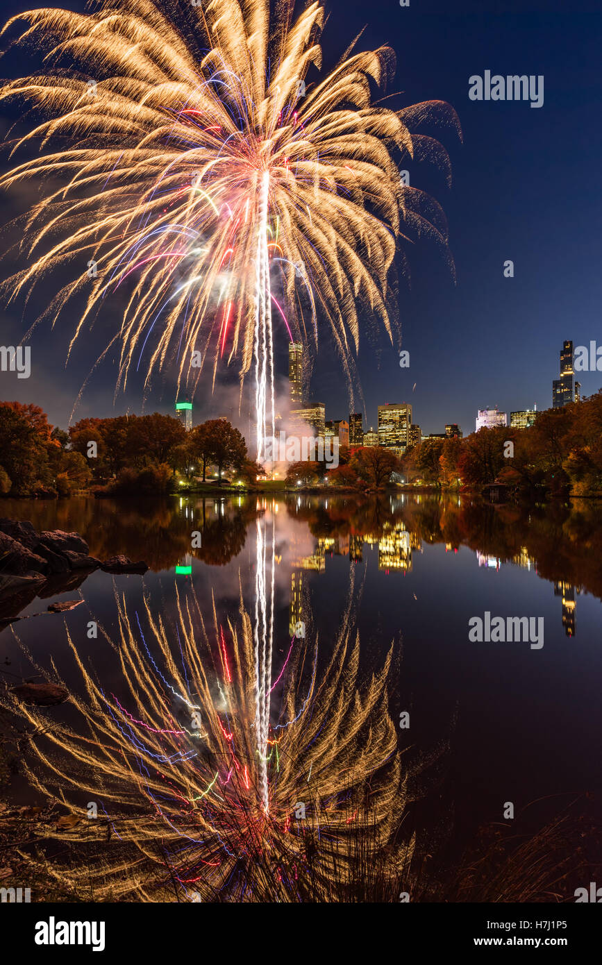 Central Park Fireworks celebrating the Marathon reflecting on the Lake. Midtown Manhattan, New York City - Stock Image