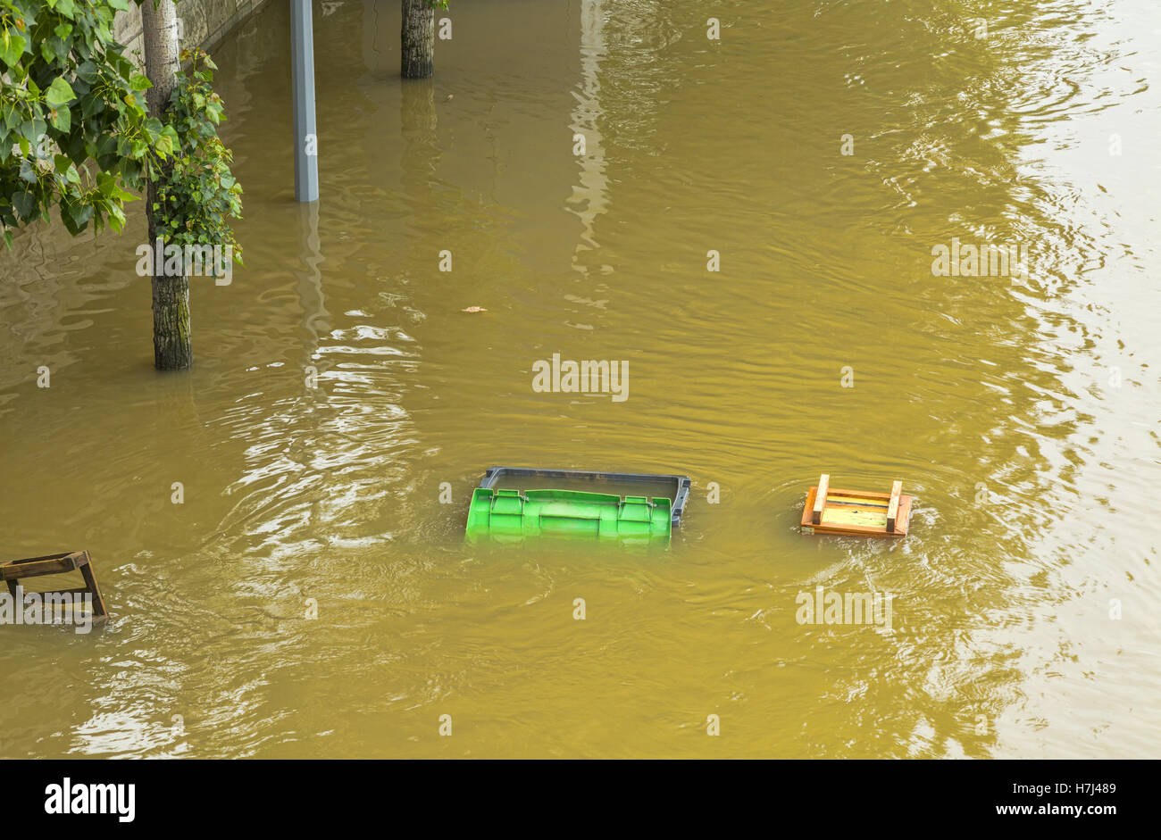 A garbage container and various wooden things are floating on the River Seine embankment after the flood - Stock Image
