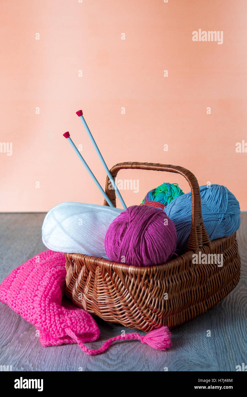 Ball of yarn and knitting needles in basket on a wooden grey table. Handmade. - Stock Image