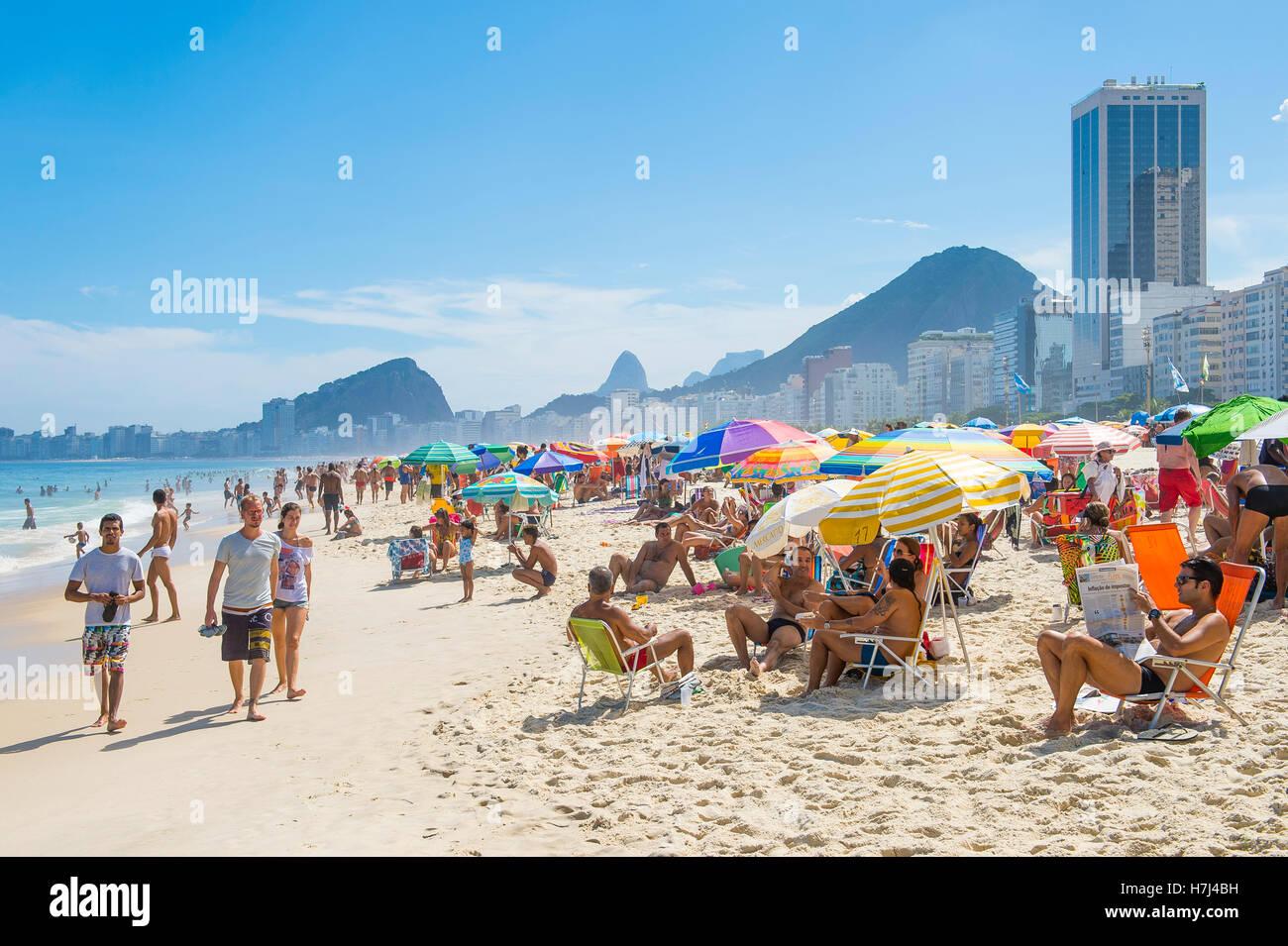 RIO DE JANEIRO - FEBRUARY 27, 2016: Crowds of beachgoers fill Copacabana Beach with colorful umbrellas on a bright - Stock Image