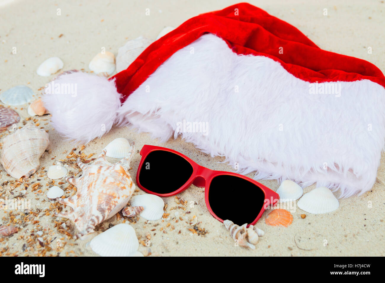 59f6cd1e Christmas hat and red sunglasses on the beach. Santa hat and eyeglasses on  the sand