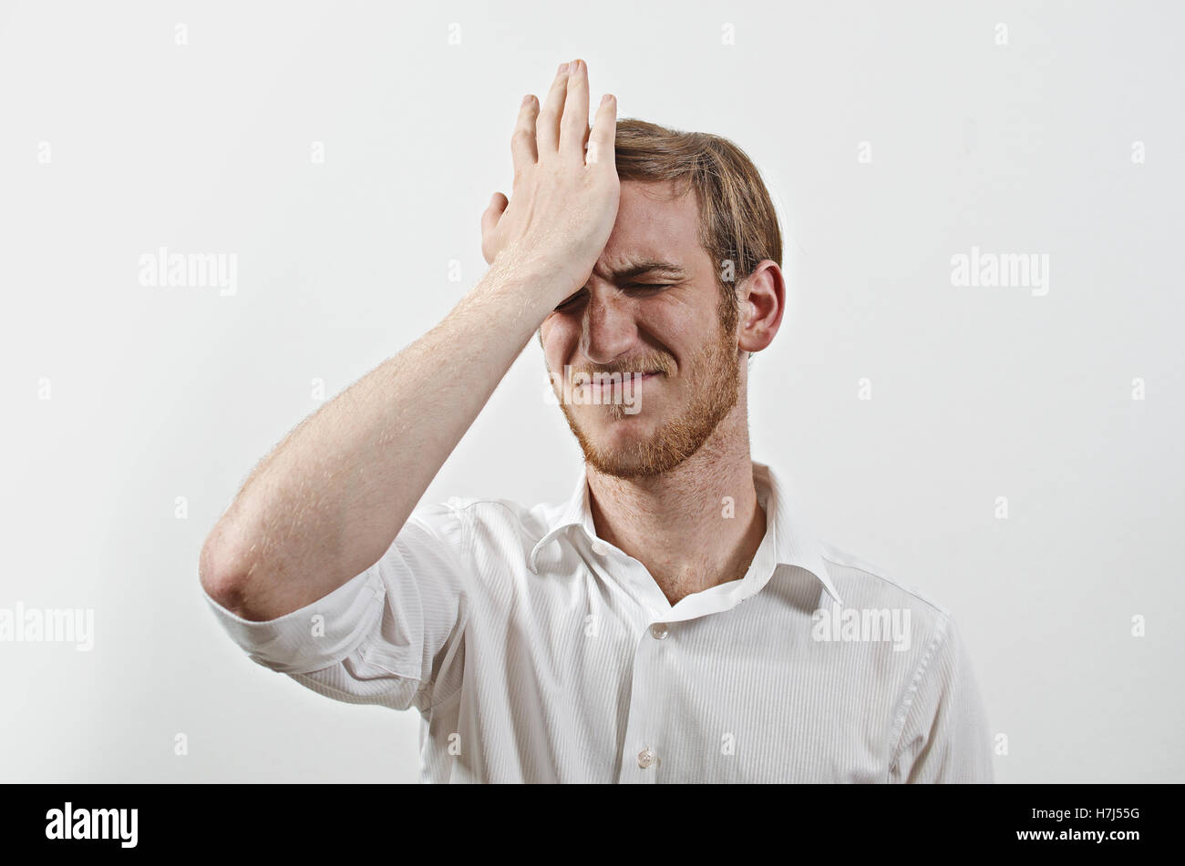 Young Adult Male Wearing White Shirt Gesturing He Has Made a Big Mistake - Stock Image