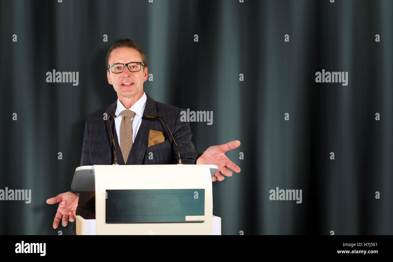 Speaker giving talk on podium at Conference - Stock Image
