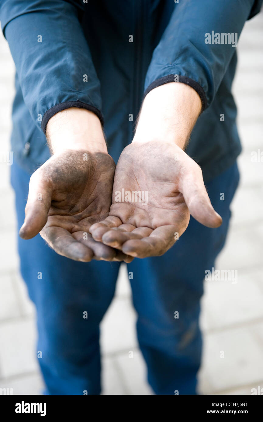 Manual labourer with dirty hands begging for money, symbolic image of an illicit worker - Stock Image