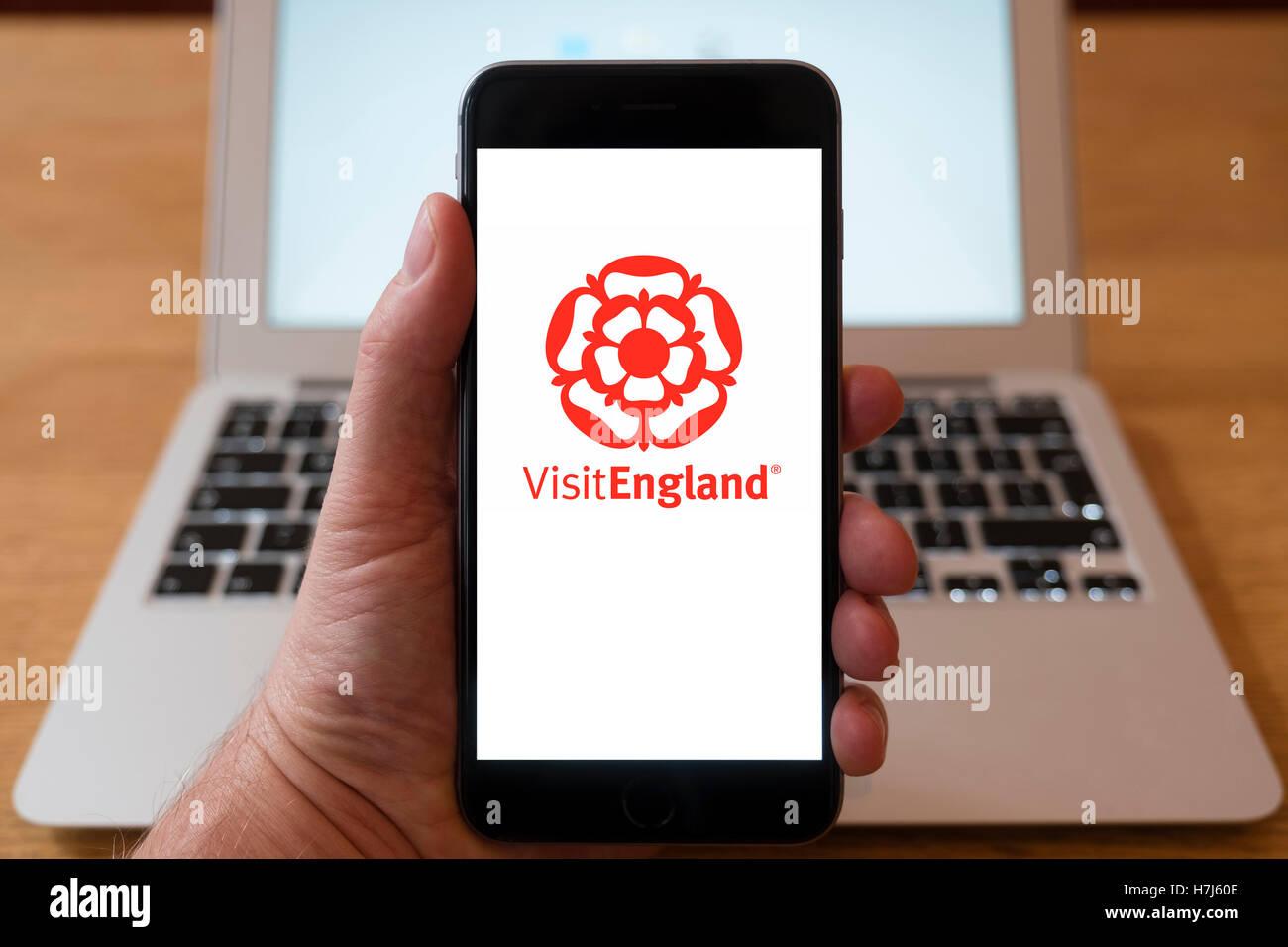 Using iPhone smart phone to display logo of Visit England tourist organisation. - Stock Image