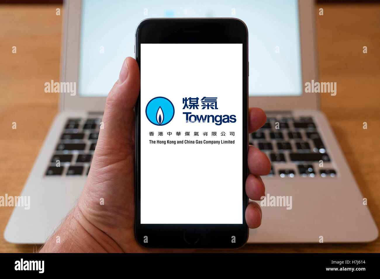 Using iPhone smart phone to display logo of Towngas, Hong Kong utility company - Stock Image