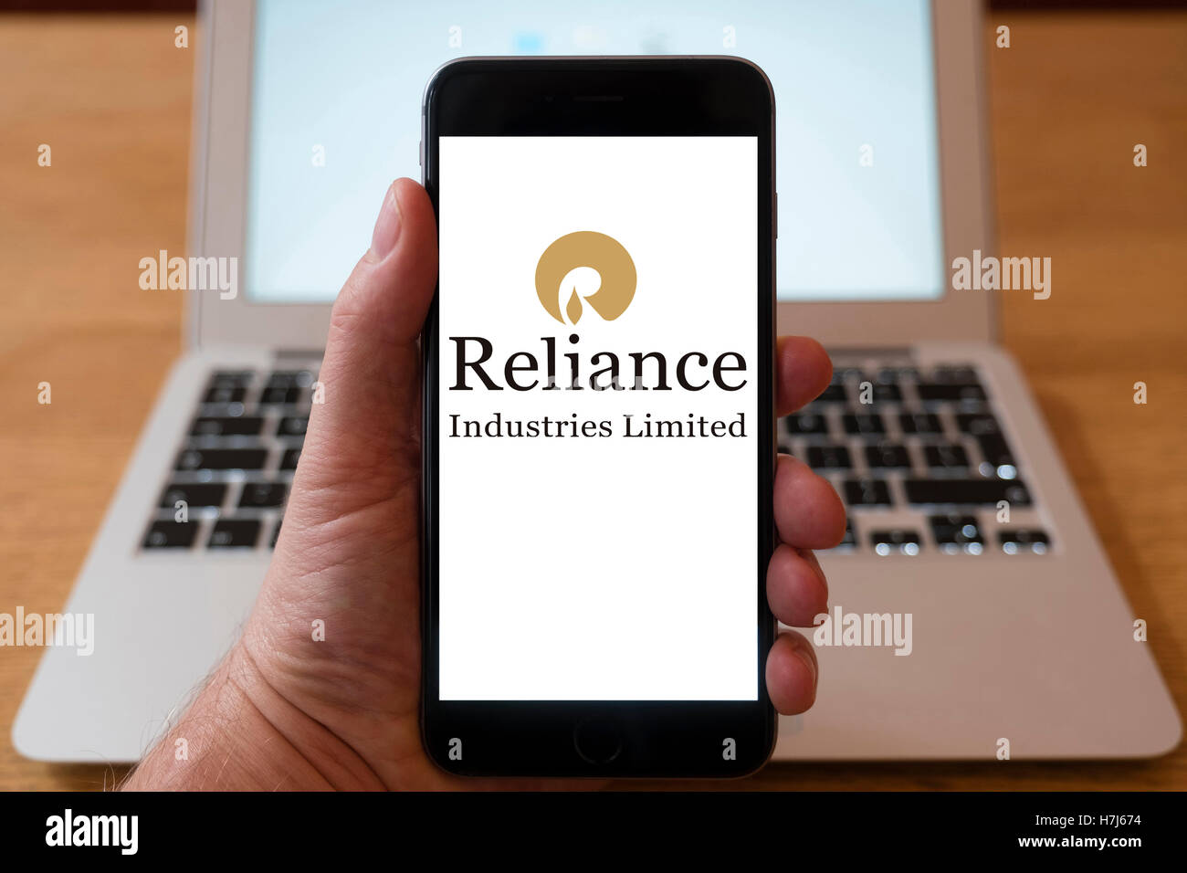 Using iPhone smart phone to display logo of Reliance Industries; Indian conglomerate holding company - Stock Image