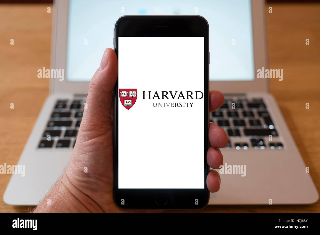 Using iPhone smart phone to display logo of Harvard University - Stock Image