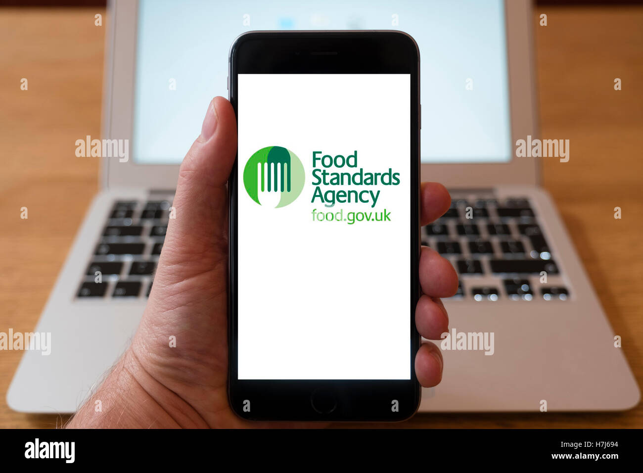 Using iPhone smart phone to display logo of the Food Standards Agency (FSA) - Stock Image