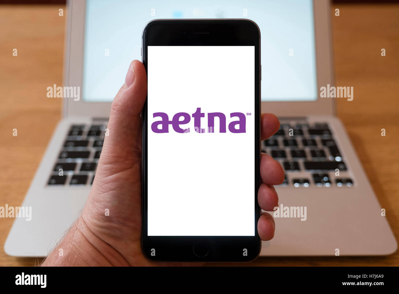 Using iPhone smart phone to display logo of Aetna; an American managed health care company - Stock Image
