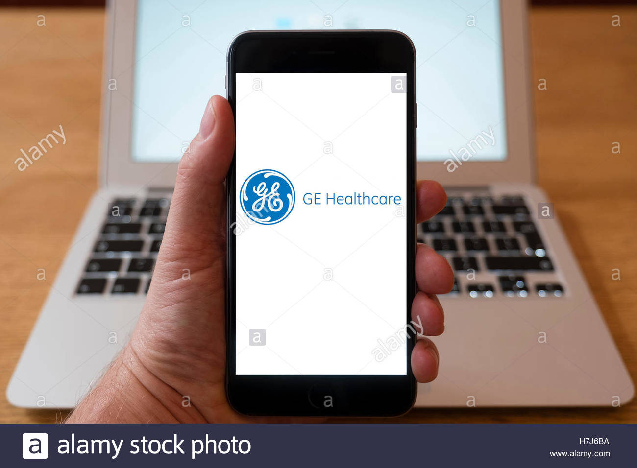 Using iPhone smart phone to display logo of GE Healthcare; Stock Photo