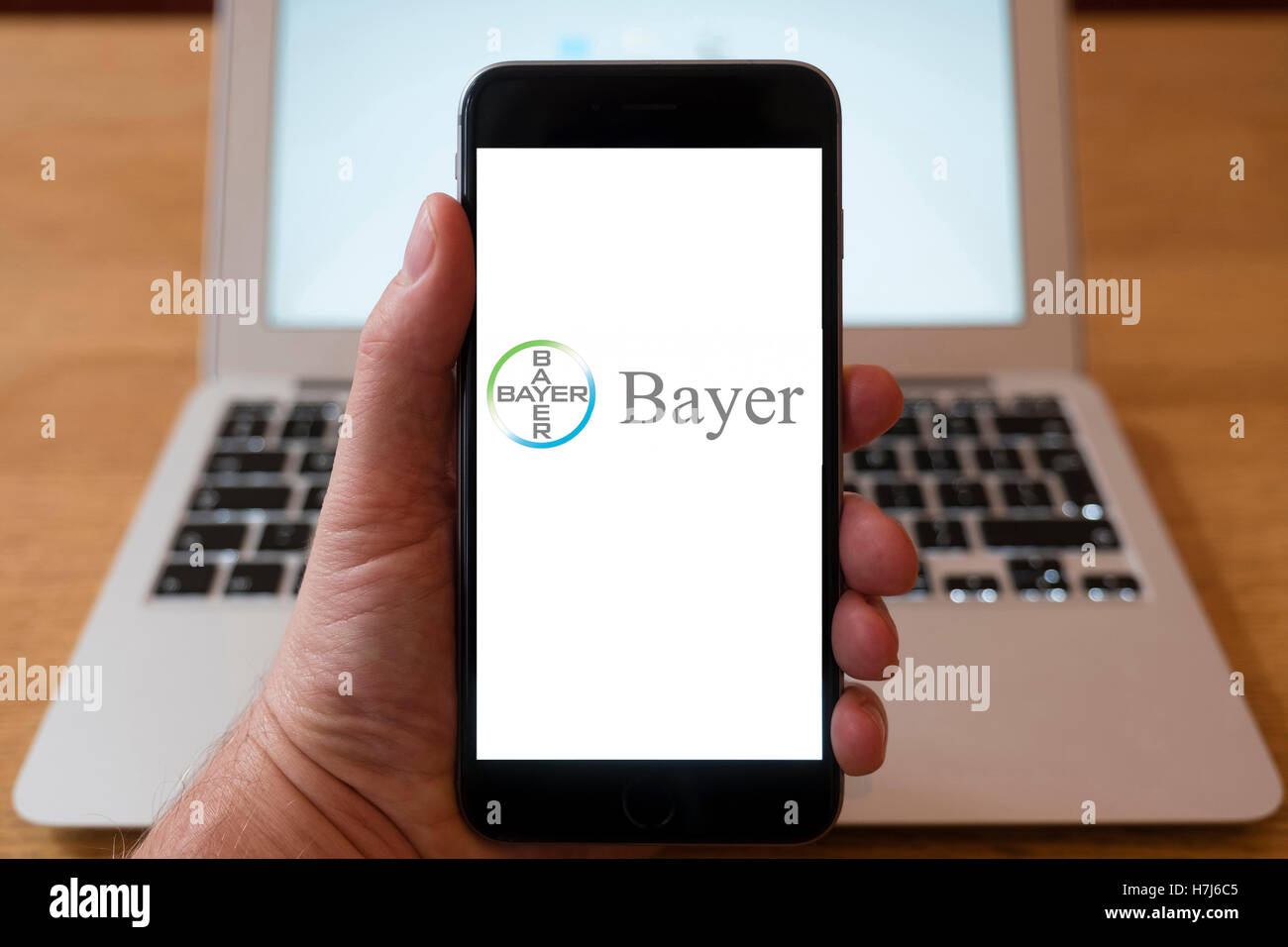 Using iPhone smart phone to display logo of Bayer pharmaceutical company - Stock Image
