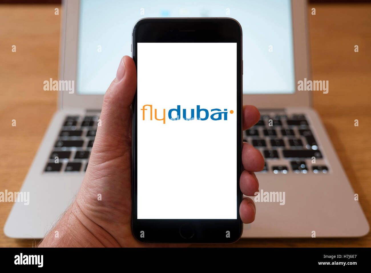 Using iPhone smart phone to display logo of Flydubai low-cost carrier from Dubai, UAE - Stock Image