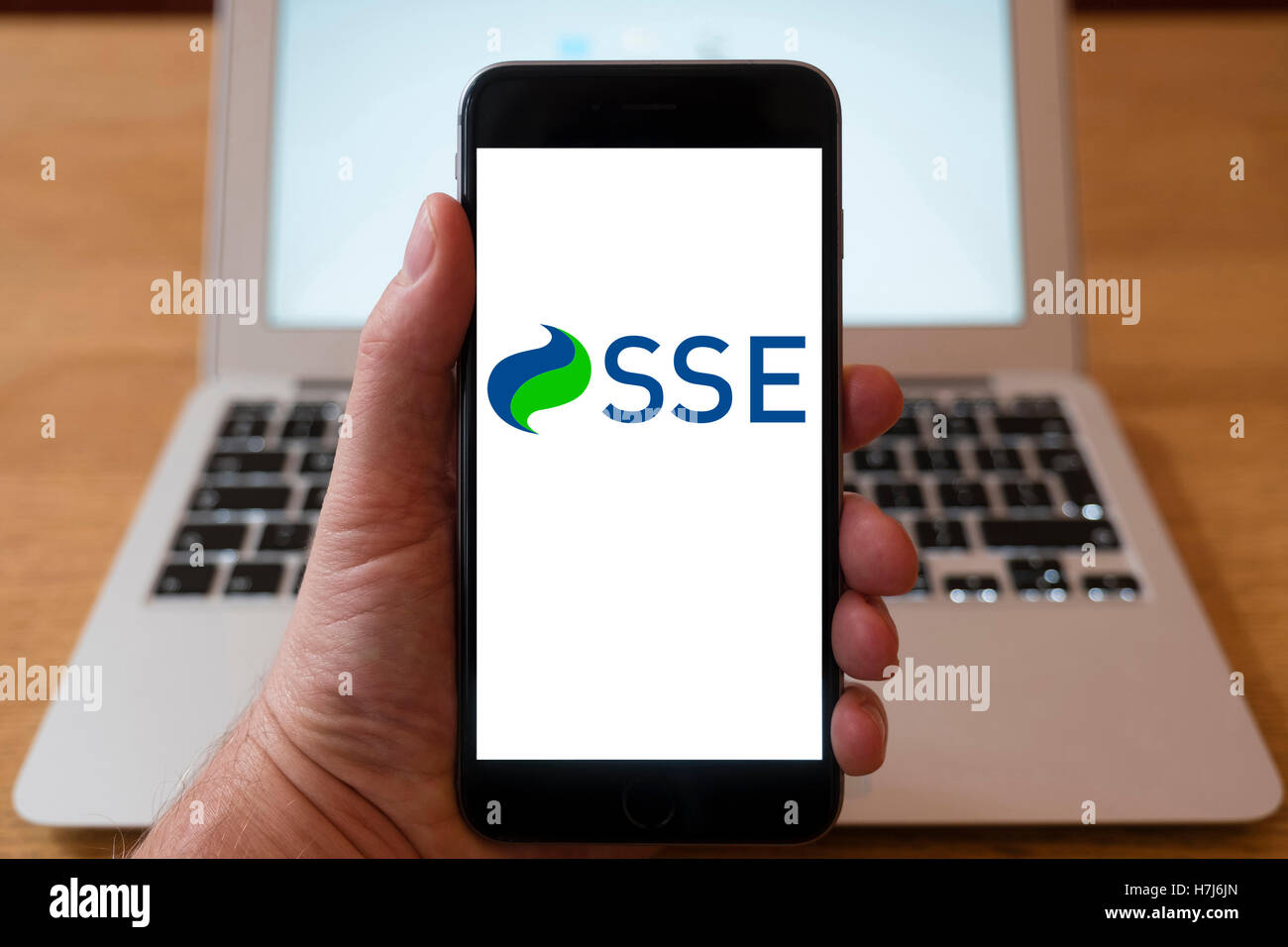 Using iPhone smart phone to display logo of SSE, energy company - Stock Image