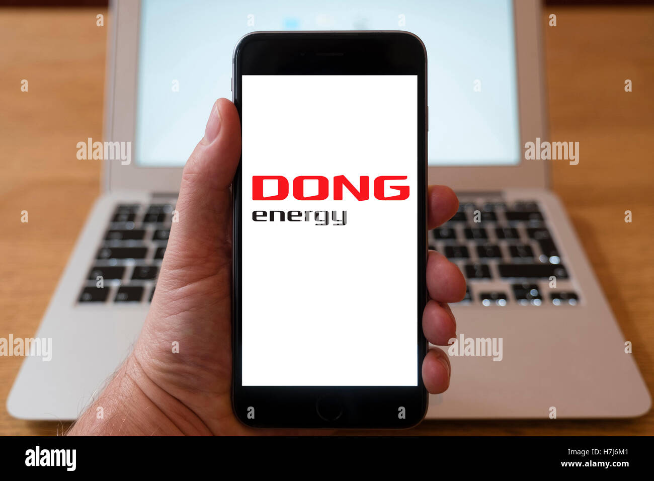 Using iPhone smart phone to display logo of Dong energy company - Stock Image